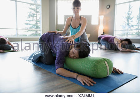 Instructor stretching womans back in restorative yoga class - Stock Photo