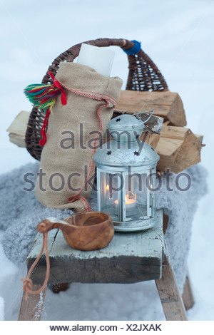 Basket, lantern, wooden cup in snow - Stock Photo