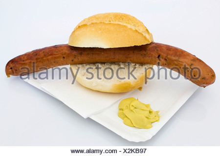 A Krakow Sausage in a bread roll with mustard on a paper plate - Stock Photo