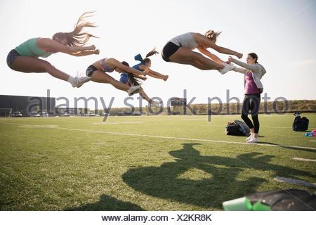 Coach guiding teenage girl high school cheerleaders jumping, practicing on sunny football field - Stock Photo