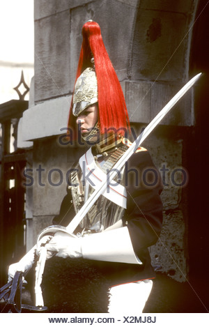 Household Cavalry soldier red plumed helmet sword ceremonial uniform British army tourist attraction London England UK guard - Stock Photo