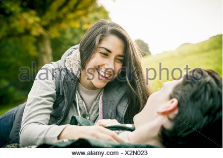 Young couple in park, laughing - Stock Photo