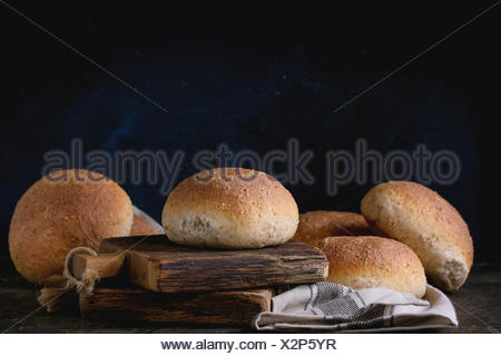 Fresh baked wholegrain buns on gray kitchen towel over small wooden chopping board with black background. - Stock Photo