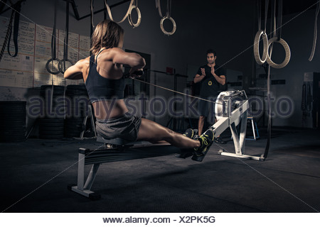Woman using rowing machine in gym - Stock Photo