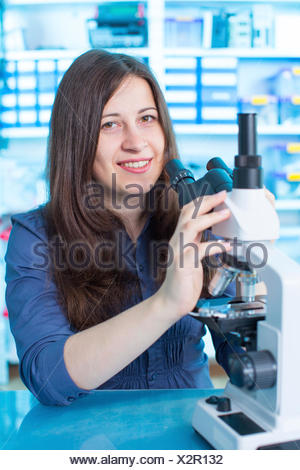 MODEL RELEASED. Young woman using microscope in the laboratory. - Stock Photo