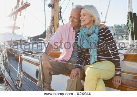 senior couple sitting on sailboat - Stock Photo