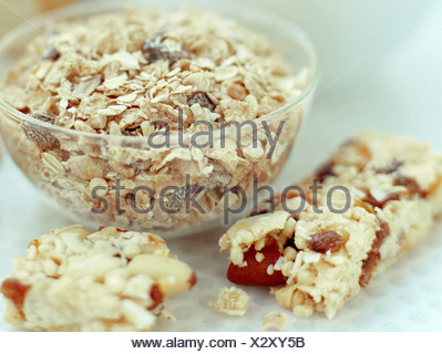 Fibre-rich foods. Cereal grains have a high fibre content and are are found in muesli (in bowl) as well as cereal bars. - Stock Photo