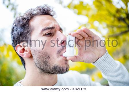 MODEL RELEASED. Young man using asthma inhaler, close-up. - Stock Photo