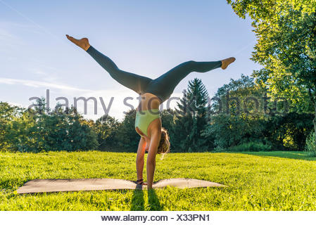 Handstand, young woman in sportswear doing workout on mat in park, Munich, Upper Bavaria, Bavaria, Germany - Stock Photo