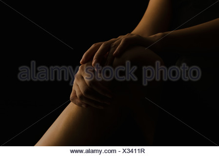 Woman's hands placed on knee, cropped - Stock Photo