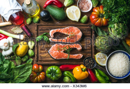 Raw uncooked salmon steak with vegetables, rice, herbs, spices and wine bottle on chopping board over rustic wooden background, - Stock Photo