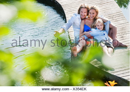 Austria, Salzburg County, Family sitting on bridge over natural pool - Stock Photo