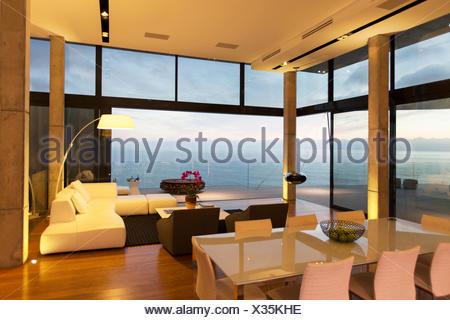 Modern living area overlooking ocean - Stock Photo