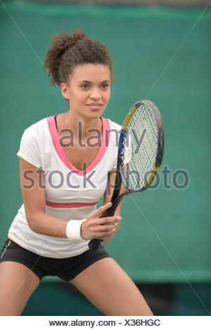 female tennis player in a receiving service stance - Stock Photo