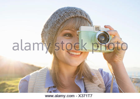 Young woman taking photograph with camera at sunset - Stock Photo