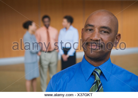 African businessman in front of coworkers - Stock Photo