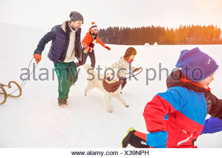 Family running in snow with dog - Stock Photo