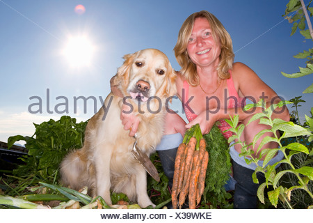 Portrait of woman and dog in vegetable garden - Stock Photo