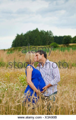 Man and a pregnant woman kissing in a field - Stock Photo