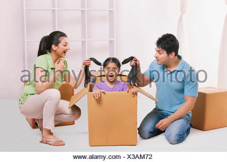 Father and mother holding daughters hair - Stock Photo