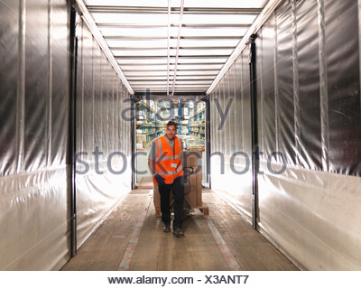Worker loads truck with pallet truck - Stock Photo