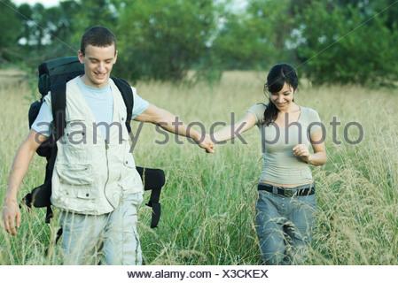 Hiking couple walking through field - Stock Photo