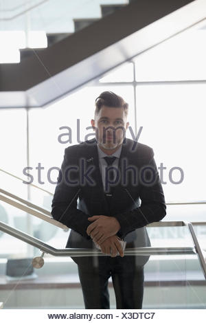 Portrait confident, serious businessman leaning on railing of office stairs - Stock Photo
