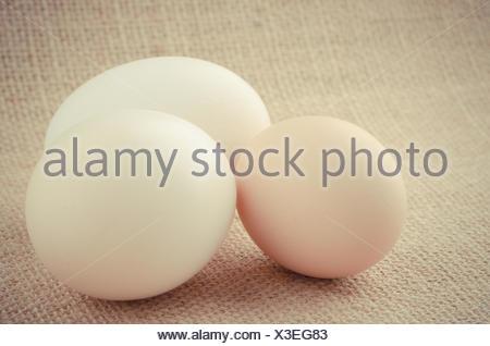 Three eggs on a raffia cloth background. - Stock Photo