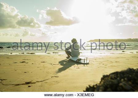 Teenage boy sitting on the beach watching sunset - Stock Photo