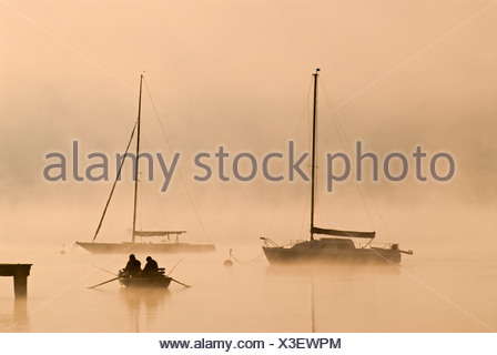 Sailing boats and fog at the southern end of Ammersee lake in Diessen, Bavaria - Stock Photo