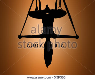 The silhouette of Young woman doing anti-gravity aerial yoga - Stock Photo