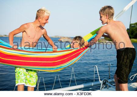 Three teenage boys (14-15,16-17) on boat deck, on of them lying in hammock - Stock Photo