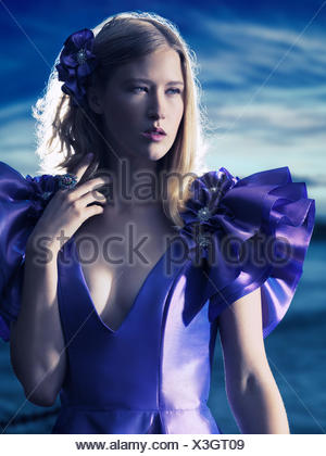 Young woman wearing an evening gown, outdoors, fashion portrait - Stock Photo