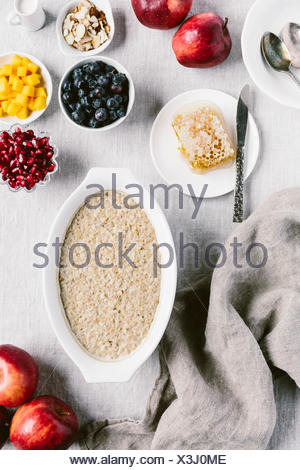 Freshly slow-cooked steel cut oats with fresh fruit toppings are photographed from the top. - Stock Photo
