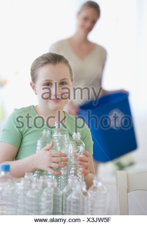 Mother and daughter filling recycle bin - Stock Photo