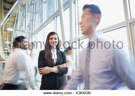 Confident businesswoman standing among busy co-workers - Stock Photo