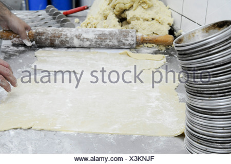 Industrial Bakery. Baker kneading and flattening dough - Stock Photo