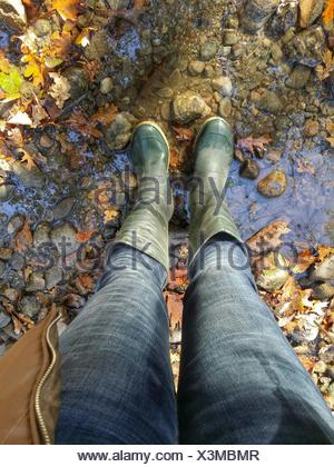 Low Section Of Woman Wearing Rubber Boot Standing On Stream - Stock Photo