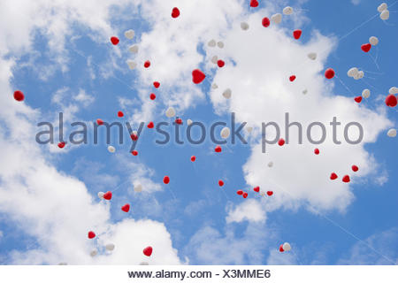 Heart-shape balloons in sky at wedding day - Stock Photo