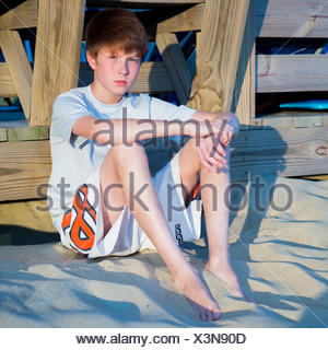Boy sitting on beach leaning against boardwalk - Stock Photo