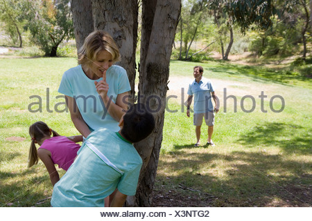 Family playing hide and seek in park mother and children 8 11 hiding behind tree father looking - Stock Photo