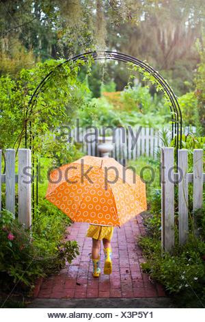 Girl walking through garden gate carrying umbrella - Stock Photo