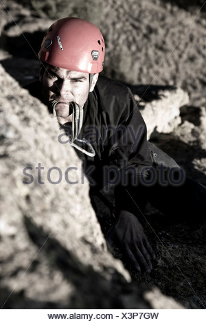 A rock climber looking towards the bolt with a quick draw in his mouth. - Stock Photo