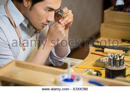 Male jeweler examining a diamond with loupe - Stock Photo