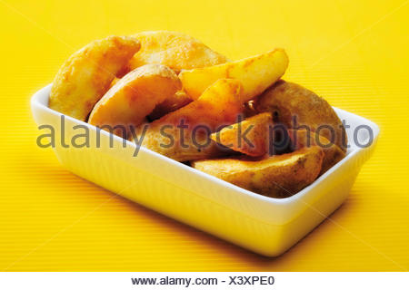 Potato wedges in porcelain bowl - Stock Photo