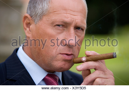 Mature businessman smoking cigar, portrait, close-up - Stock Photo