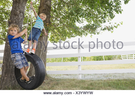 Playful boys standing on tire swing - Stock Photo