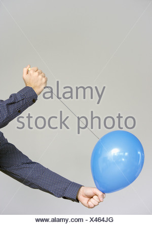men's hands about to burst a balloon - Stock Photo