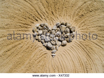 Heart made of pebbles in sand - Stock Photo