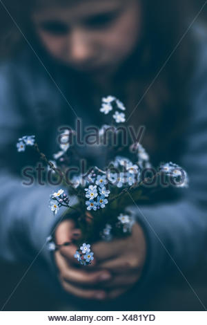 Norway, Girl (8-9) holding bouquet of forget-me-not flowers - Stock Photo